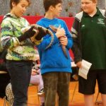 Students holding reptiles while doing a presentation.