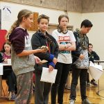 Four students with reptiles giving a presentation.