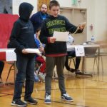 Two students giving a presentation about a reptile.