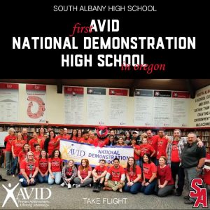 Students and staff gather with the AVID flag.